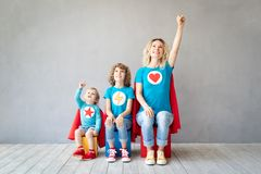 Familie van superheroes die thuis spelen stock fotografie
