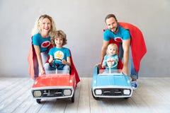 Familie van superheroes die thuis spelen stock foto's