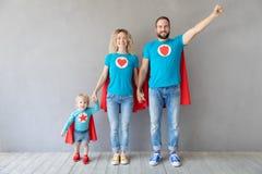 Familie van superheroes die thuis spelen stock afbeelding
