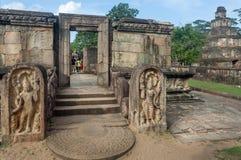 Familie van toeristen die rond geruïneerde stad met de boeddhistische tempel van de de 12de eeuwbaksteen, Sri Lanka letten op Oud stock afbeelding
