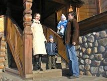 Familie van vier bij trap van groot houten huis Stock Foto's