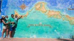 Familie van vier dichtbij grote kaart van Caraïbisch eiland stock afbeeldingen