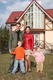 Familie van vier dichtbij huis Stock Foto's