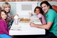 Familie van vier die aan camera stellen stock foto