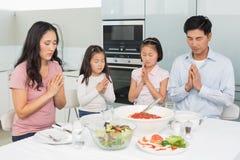 Familie van vier die gunst zeggen vóór maaltijd in keuken royalty-vrije stock foto