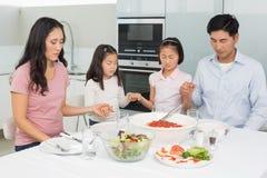 Familie van vier die gunst zeggen vóór maaltijd in keuken royalty-vrije stock fotografie