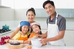 Familie van vier die koekjes in keuken voorbereiden Royalty-vrije Stock Afbeeldingen