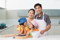 Familie van vier die koekjes in keuken voorbereiden Royalty-vrije Stock Foto