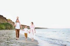 Familie van vier die langs de kust lopen ouders en twee zonen Gelukkige vriendschappelijke familie stock fotografie