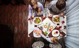 Familie van vier die maaltijd hebben bij een restaurant stock afbeeldingen