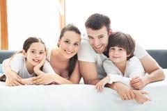 Familie van vier die op bed liggen Stock Foto's