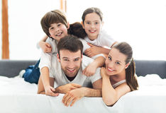 Familie van vier die op bed liggen Royalty-vrije Stock Foto