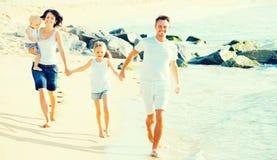 Familie van vier die op zandig strand op zonnig weer lopen Royalty-vrije Stock Foto