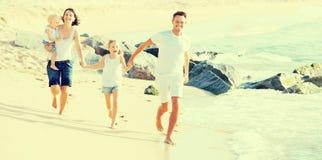 Familie van vier die op zandig strand op zonnig weer lopen Royalty-vrije Stock Fotografie