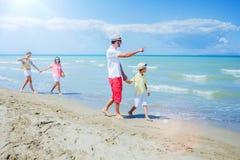 Familie van vier die pret hebben bij het strand Royalty-vrije Stock Afbeelding