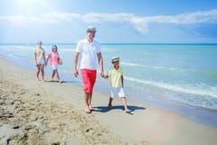 Familie van vier die pret hebben bij het strand Royalty-vrije Stock Foto's