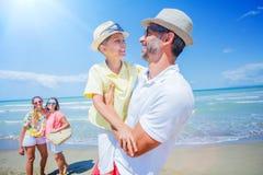 Familie van vier die pret hebben bij het strand Royalty-vrije Stock Afbeeldingen