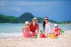 Familie van vier die zandkasteel maken bij tropisch wit strand stock foto