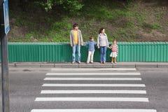 Familie van vier die zich dichtbij oversteekplaats bevinden Stock Foto