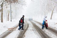 Familie van vier die zorgvuldig die de straat kruisen met sneeuw en modder wordt behandeld stock foto