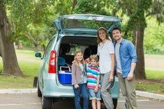 Familie van vier door autoboomstam terwijl op picknick Royalty-vrije Stock Afbeelding