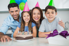 Familie van vier met cake en giften bij verjaardagspartij Stock Afbeeldingen