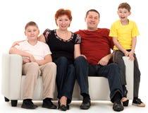 Familie van vier op een bank stock afbeelding