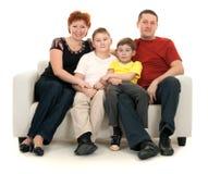 Familie van vier op een bank royalty-vrije stock afbeelding