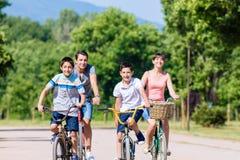 Familie van vier op fietsreis in de zomer stock fotografie