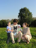 Familie van vier op gras houten blauwe hemel royalty-vrije stock foto