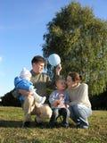 Familie van vier op herfst 2 van de gras de blauwe hemel stock afbeelding