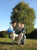 Familie van vier op herfst 3 van de gras de blauwe hemel stock foto's
