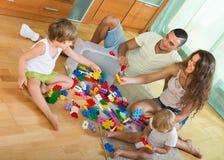 Familie van vier thuis met speelgoed Stock Foto's