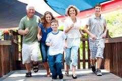 Familie van vijf die op de houten brug lopen Stock Foto