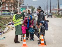 Familie van vluchtelingen die met een NGO-vrijwilliger op hun manier bespreken om Servië te registreren en in te gaan bij grens m stock afbeeldingen