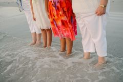 Familie van Vrouwen die buiten Onder ogen ziend de Oceaan in Ondiep Wateroever bij het Strand op Vakantie in Aard bevinden zich royalty-vrije stock afbeelding