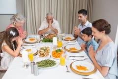 Familie van zes die gunst zeggen vóór maaltijd bij eettafel stock foto