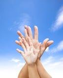 Familie verenigde handen met blauwe hemel en wolk Stock Afbeeldingen