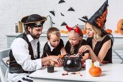 Familie in verschiedenen Halloween-Kostümen bei Tisch mit schwarzem Topf mit Festlichkeiten in der Küche stockbild