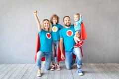 Familie von den Superhelden, die zu Hause spielen lizenzfreies stockfoto