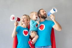 Familie von den Superhelden, die zu Hause spielen lizenzfreie stockfotos