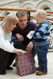 Familie von drei Personen, die Paket betrachten Lizenzfreies Stockbild