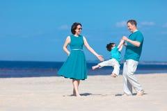 Familie von drei Spaß auf Strand habend Stockfoto