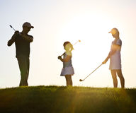 Familie von Golfspieler bei Sonnenuntergang Lizenzfreies Stockbild
