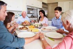Familie von mehreren Generationen, die Gebet sagt, bevor Mahlzeit gegessen wird Stockfotos