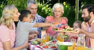 Familie von mehreren Generationen isst im Garten stock video