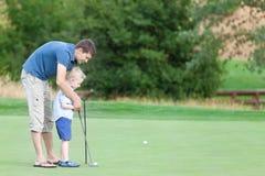 Familie von zwei am Golfplatz Stockbilder