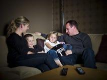 Familie vor dem Fernsehapparat stockbild