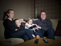 Familie vor dem Fernsehapparat stockbilder
