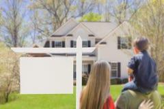 Familie vor leerem Real Estate-Zeichen und -haus Stockfotografie